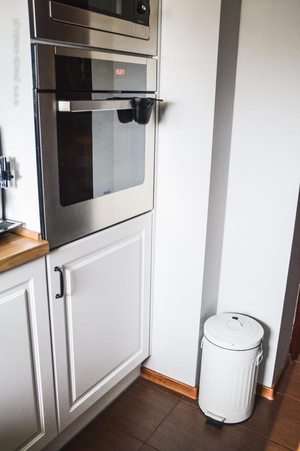 Mała kuchnia z białymi frontami i drewnianym blatem